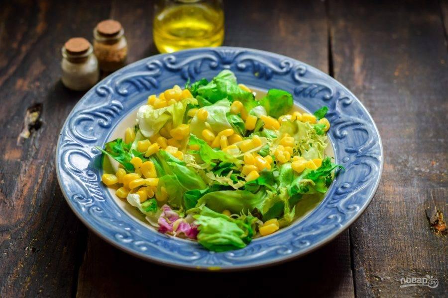 Поверх листьев салата выложите кукурузу.