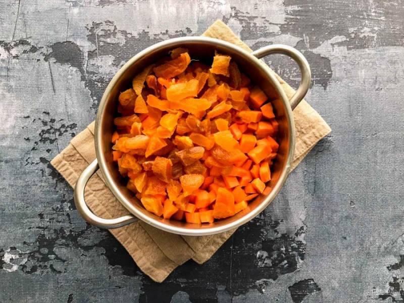 В кастрюлю выложите нарезанную на небольшие кусочки морковь и курагу.