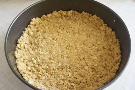 2. Смешаем крошку с растопленным сливочным маслом, формируем корж, чуть залезая на бортики  формы.