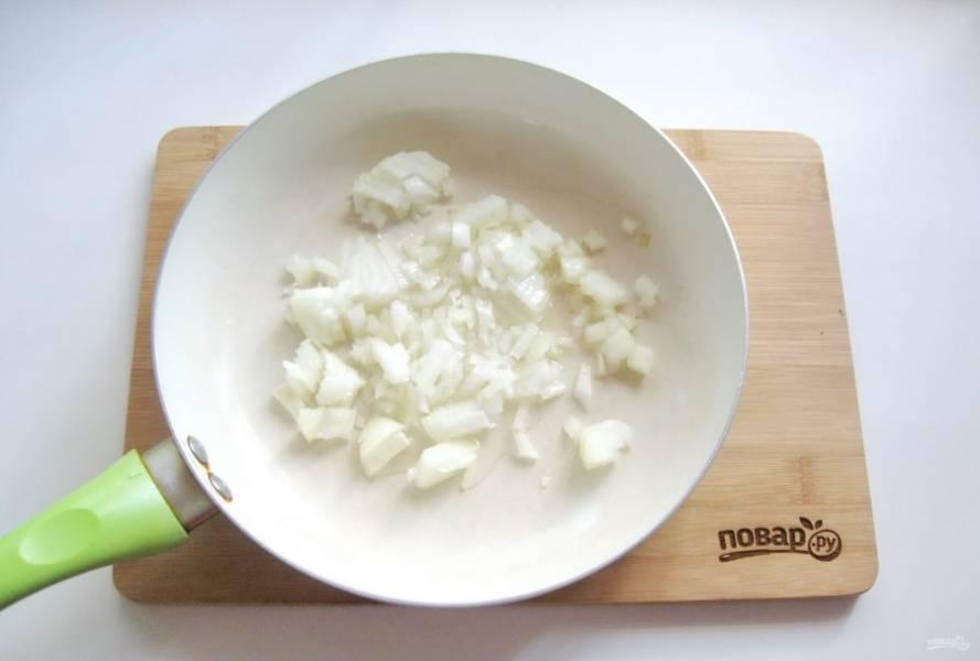 Пока тесто подходит, приготовьте начинку. Репчатый лук очистите, помойте и мелко нарежьте. Выложите в сковороду.