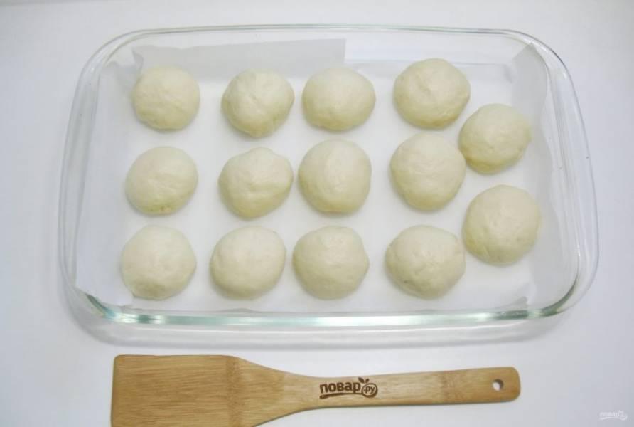 Выложите шарики теста в форму для выпечки. Накройте пищевой пленкой и дайте постоять в тепле или при комнатной температуре 25-30 минут.