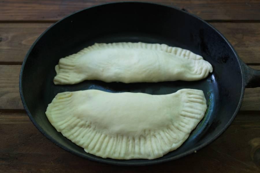 В сковороду влейте 1 ч. ложку растительного масла. Смажьте всю сковороду. Больше масло нам не понадобится. Обжарьте все чебуреки на горячей сковороде с двух сторон.