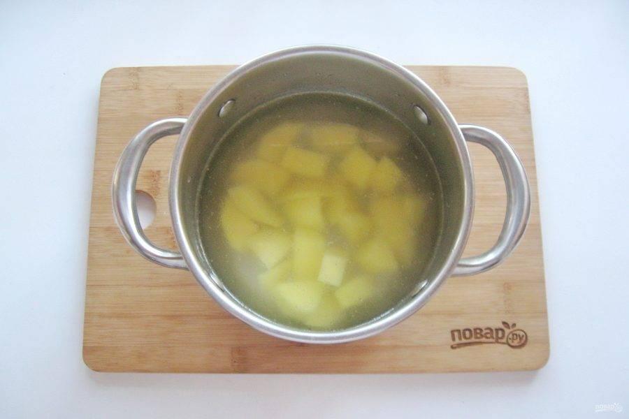 Если есть необходимость, бульон процедите. Картофель очистите, помойте и нарежьте кубиками. Выложите в кастрюлю с бульоном и начинайте варить суп.