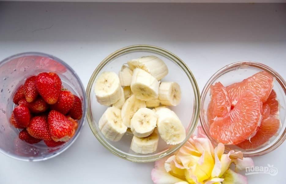 Банан почистите и крупно нарежьте. Клубнику тщательно промойте, убрав листья. Грейпфрут очистите от плёнок. Лепестки промойте и обсушите.