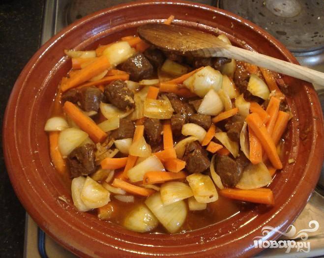 3.Разогреть оставшееся оливковое масло в горшочку на среднем огне. Добавить 1/3 баранины и хорошо подрумянить. Повторить еще два раза, потом добавить лук и морковь и готовить 5 минут.  Чеснок выдавить и добавить в горшочек. Добавить имбирь и готовить еще 5 минут. Добавить лимонную цедру, куриный бульон, томатную пасту и мед.