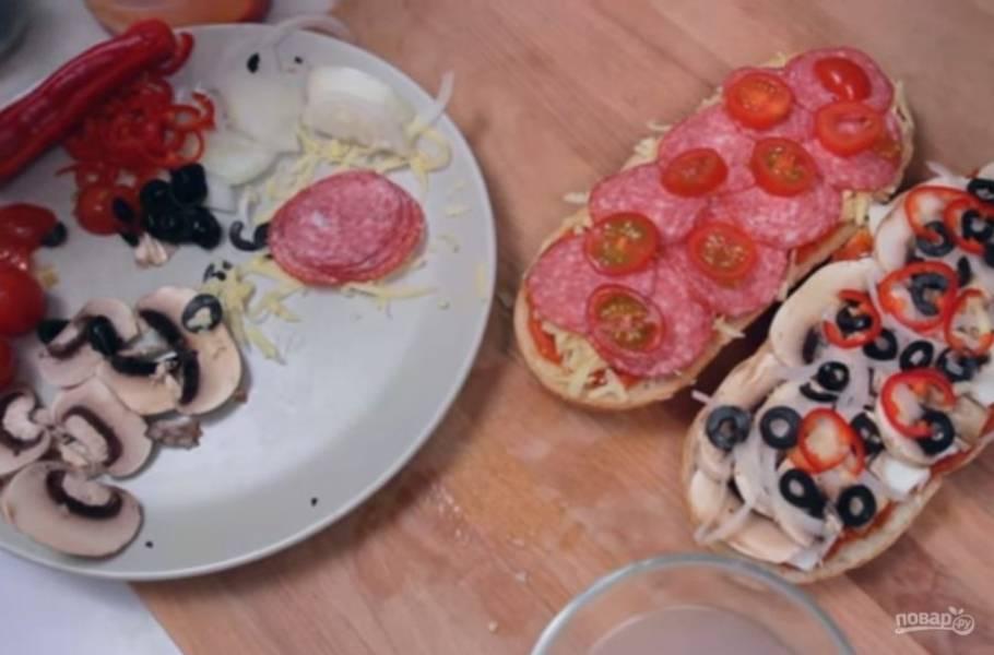 3. Ломтики хлеба обильно смажьте томатным соусом и выложите начинку: на один ломтик положите натертую моцареллу, шампиньоны, лук и маслины, на вторую — натертый твердый сыр, колбасу, помидоры и маслины.