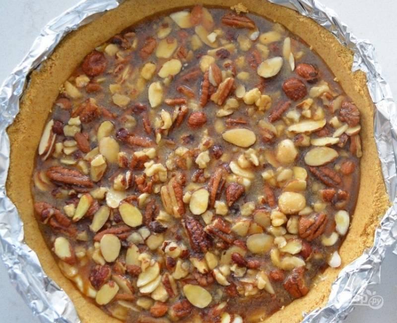 6. Аккуратно распределите карамель с орешками на сливочный крем. Запекайте чизкейк в духовке в течение часа. После приготовления обязательно остудите десерт при комнатной температуре.