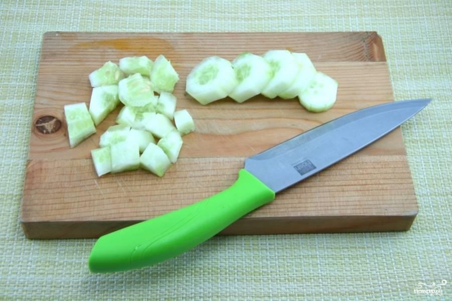 Почистите огурец от кожуры. Нарежьте сначала кружками, а потом четвертинками.