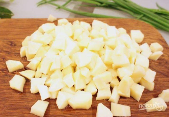 Картофель очистите от кожуры и вымойте под проточной водой. Влейте в кастрюлю чистую питьевую воду, выложите в нее картофель, нарезанный кубиками.