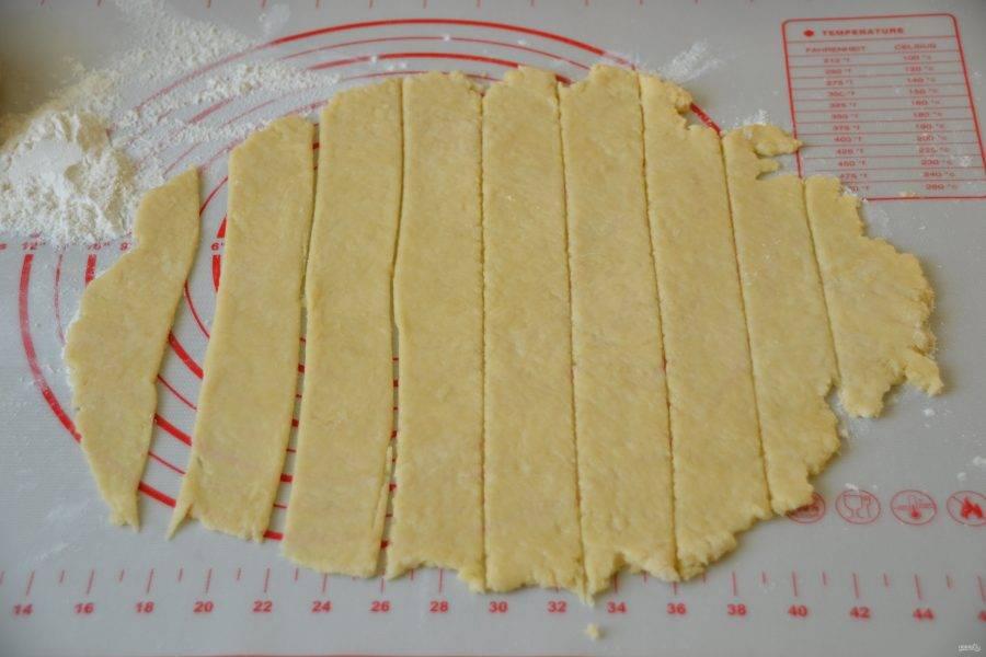 Разделите тесто на 2 части (так удобнее работать). Раскатайте в пласт и нарежьте полоски шириной 1,5-2 см.