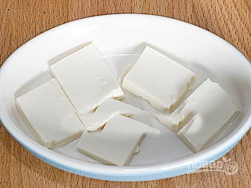 """3. В емкость для выпекания положите в один слой толсто нарезанные ломтики тофу. Сверху насыпьте фарш и посыпьте натертым сыром """"Моцарелла""""."""