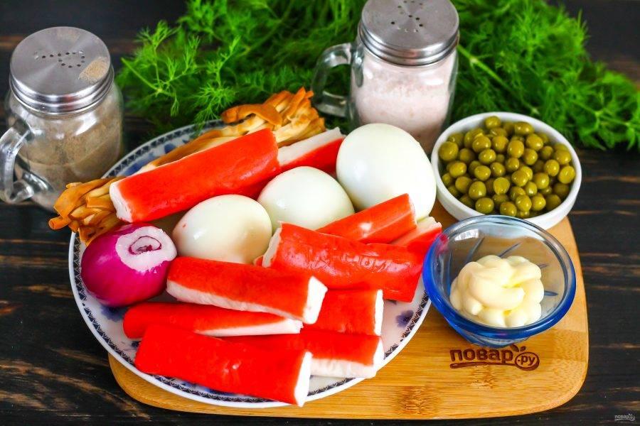 Подготовьте указанные ингредиенты. Крабовые палочки заранее разморозьте, куриные яйца отварите и остудите, очистите.