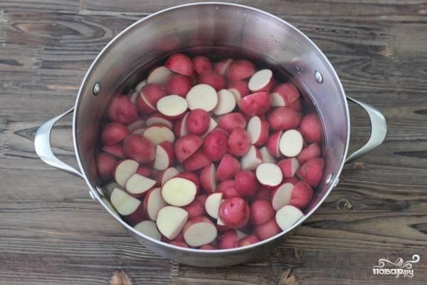 2. Картофель вымойте, при необходимости очистите (молодой можно запекать в кожуре) и нарежьте небольшими кусочками. Выложите в кастрюлю с водой, доведите до кипения и проварите минут 10 на среднем огне.