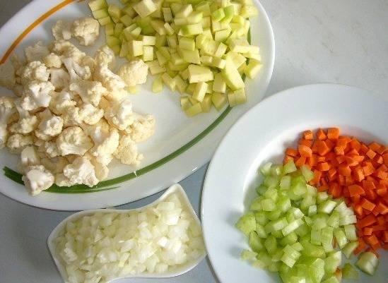Далее чистим и промываем овощи. Репчатый лук, кабачок, морковь и сельдерей режем на кубики, цветную капусту разбираем на соцветия.