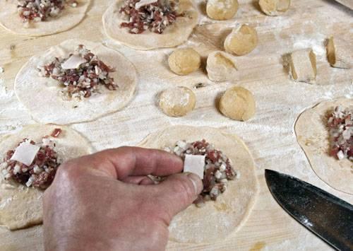 8. Когда все лепешки готовы, можно выкладывать на них начинку. Чтобы манты были сочнее, сверху можно выложить небольшой кусочек сала.