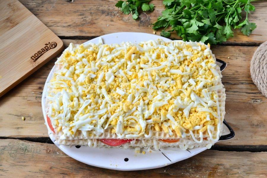 Сверху положите последний вафельный лист. Щедро смажьте его майонезом и присыпьте натертыми на крупной терке яйцами.