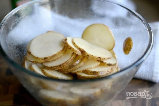 1. Тщательно промытый картофель нарежьте тонкими кружками. Перемешайте с маслом.