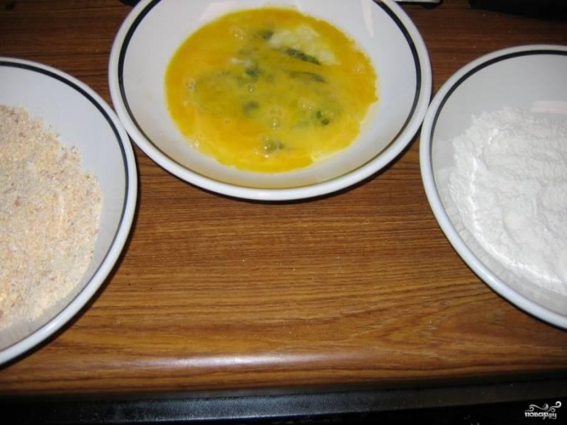 Подготовьте ингредиенты: в отдельной миске взбейте яйца, добавьте к ним приправу. Насыпьте в другую миску муку, добавьте соль и перец. Рядом поставьте миску с кукурузной мукой.  Филе проверьте на наличие костей. Удалите лишние.  Поставьте разогреваться сковороду с растительным маслом.
