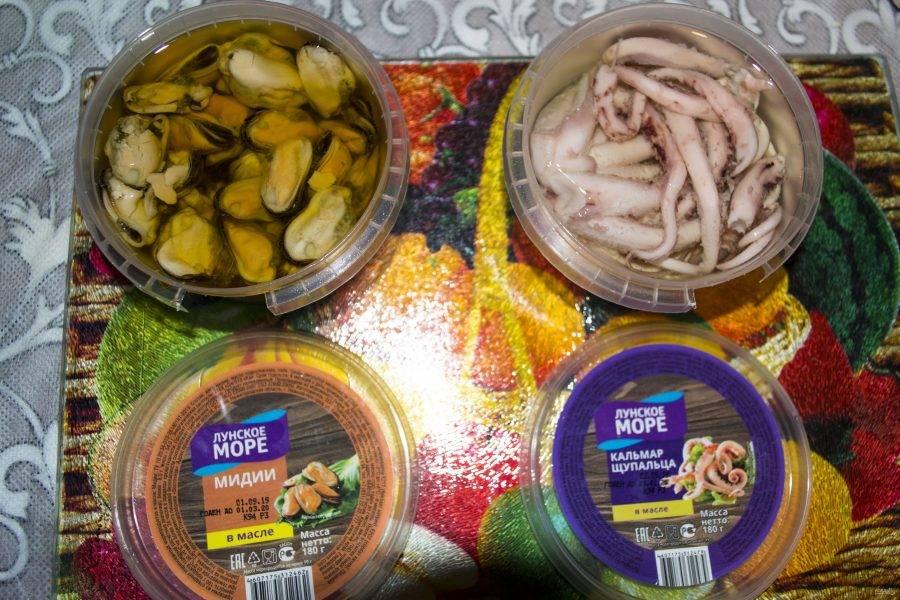 Морепродукты в нашем случае уже готовы, что существенно экономит нам время, поэтому их остается только открыть. Поскольку мы используем кальмары и мидии в масле, то при выкладывании старайтесь чтобы масло с них стекло.
