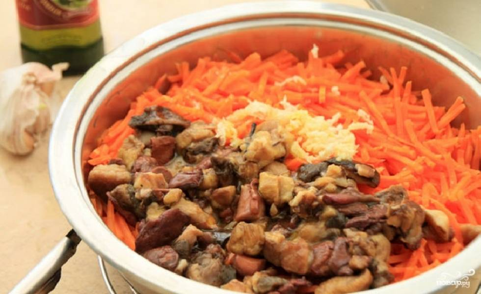 Через 15 минут откройте крышку и добавьте в кастрюлю мелко порезанные грибы, выдавленный чеснок, специи, соль и пару ложек растительного масла.