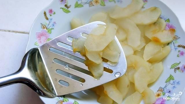 Затем шумовкой аккуратно вынимаем дольки яблок из сиропа, выкладываем их на тарелку, пусть остывают.