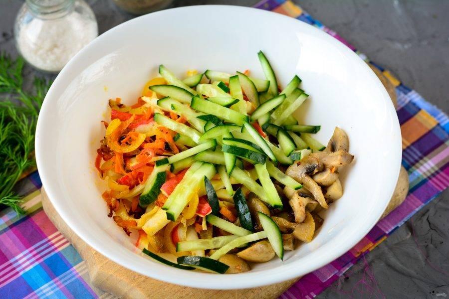 В пиалу выложите жареные грибы, лук с морковкой и крабовыми палочками. Также добавьте огурцы, нарезанные полосками.