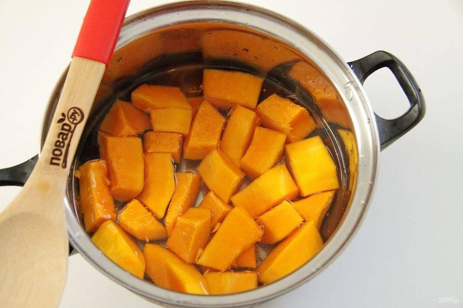 При помощи столовой ложки извлеките у тыквы семена. Нарежьте мякоть тыквы кусочками и сложите в небольшую кастрюльку. Залейте водой, чтобы она лишь слегка ее покрывала.