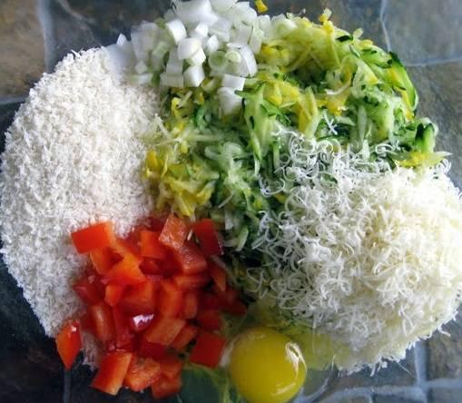 3. В большую миску выложите тертые кабачки, нарезанный кубиками болгарский перец, измельченные перышки лука, вбейте яйцо, добавьте тертый сухари, тертый сыр, соль и специи. Все хорошенько перемешайте.