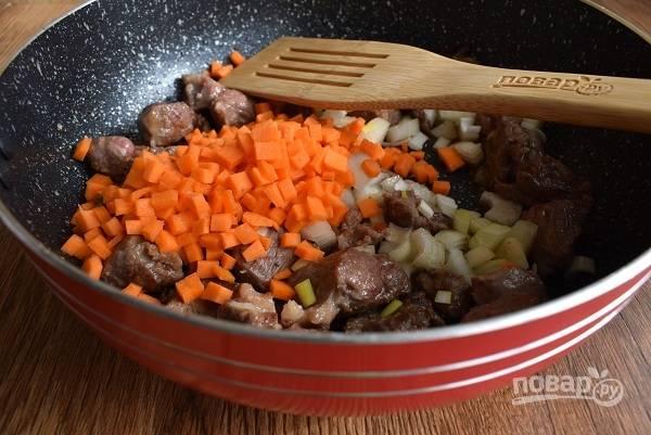 Морковь нарежьте кубиками, отправьте в сковороду, готовьте 5 минут.