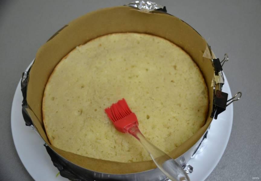 Выложите бисквит в разъемное кольцо, стенки проложите пленкой или бумагой для выпечки, смажьте бисквит сахарной пропиткой.
