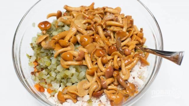 7. В глубоком салатнике соедините курицу и огурчики. Следом выложите грибочки.