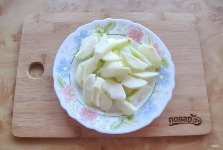 Крупное яблоко помойте, очистите, удалите семена и нарежьте пластиночками.