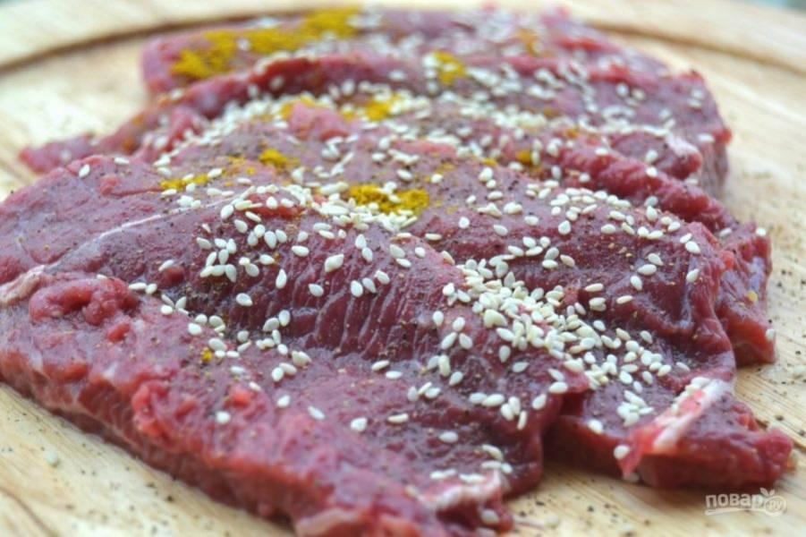 2.Добавьте к мясу соль, перец, кунжут и карри, тщательно обмажьте мясо приправами.