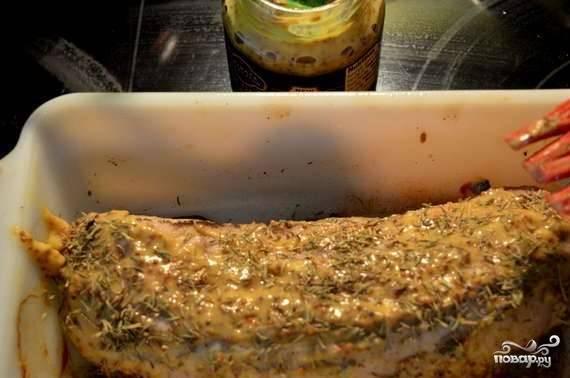 Достаньте мясо, дайте ему немного остыть. Обмажьте его горчицей и присыпьте травами.