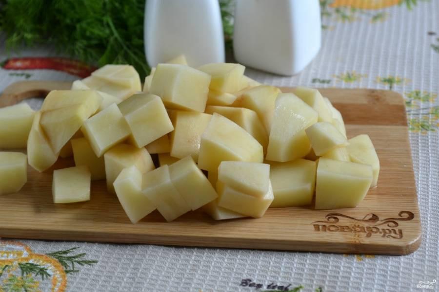 Нарежьте картофель кубиками небольшого размера, добавьте его в чашу мультиварки.