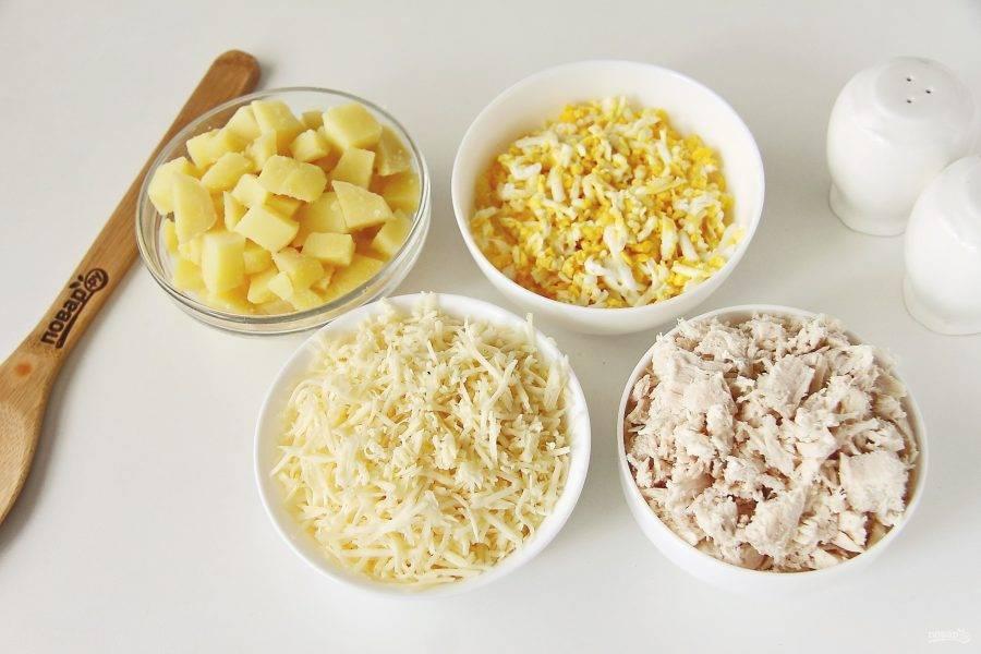 Картофель и филе нарежьте небольшими кубиками. Яйца натрите на крупной терке, сыр на мелкой.