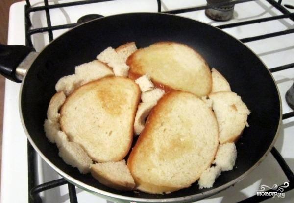 4.На сковороду наливаем несколько капель масла, укладываем в неё целые ломтики хлеба. Пространство между ними заполняем кусочками батона. Обжариваем до появления легкой корочки, после чего переворачиваем на другую сторону.