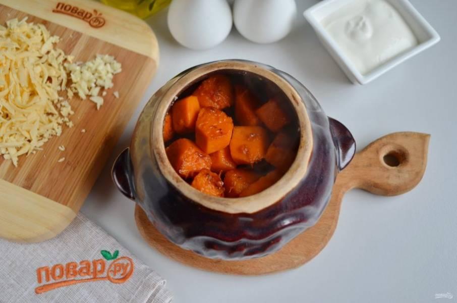 Порубите мелко чеснок, натрите на терке сыр. В горшочек на дно уложите печень с луком, далее — тыкву.
