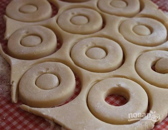 5. А дальше все очень просто: разогрейте духовку до 180 градусов, а тесто раскатайте тонким пластом. Вырежьте печеньки. В данном случае это колечки, но вы можете использовать любые выемки.