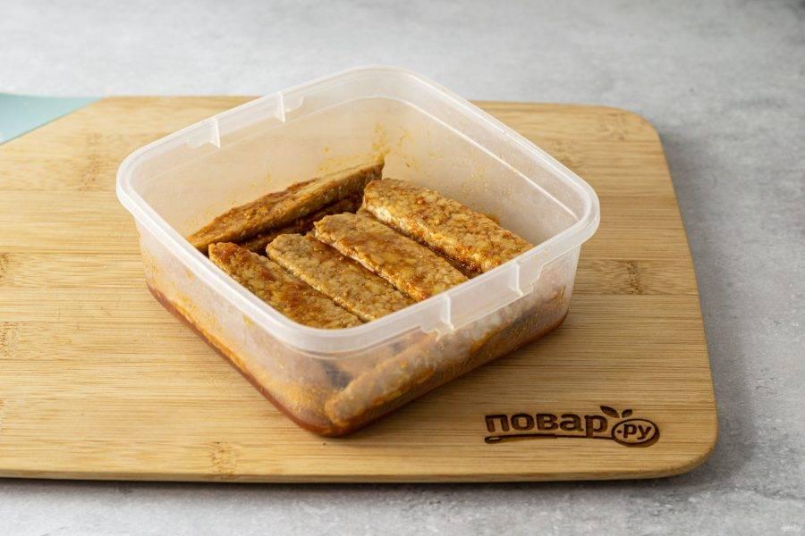 Выложите полоски темпе в пищевой контейнер и полейте их маринадом. Оставьте на 1 час в холодильнике.