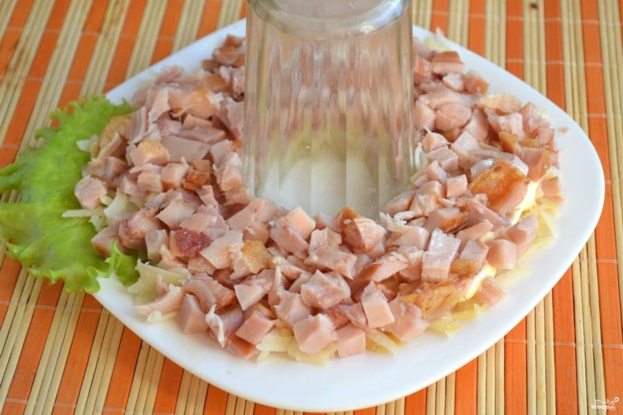 Мясо курицы отделите от кости, измельчите и выложите вторым слоем. Сверху смажьте майонезом.
