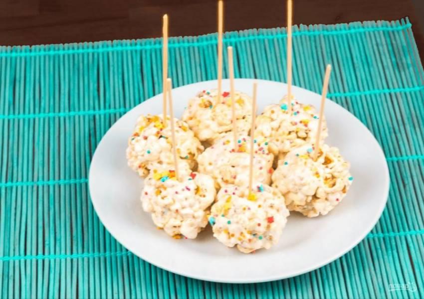 5. Каждую конфету проткните деревянной шпажкой и украсьте кондитерской посыпкой. Затем отправьте конфеты в холодильник на полчаса, чтобы они застыли. Приятного аппетита!