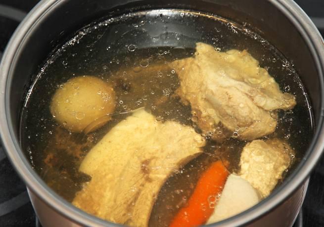 Мясо промываем и складываем в кастрюлю, добавляем одну луковицу, одну морковь, несколько горошин перца, соль и лавровый лист. Доводим бульон до кипения и варим на медленном огне 1 час.