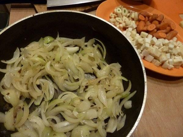 На сковороду, в которой обжаривалось мясо, выкладываем нарезанный перьями репчатый лук и жарим его до прозрачности.