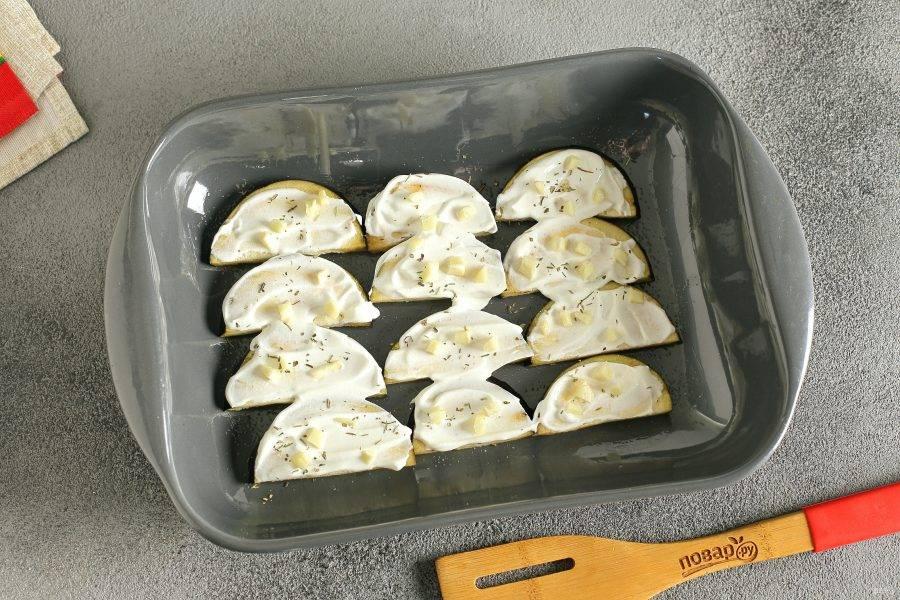 Баклажаны смажьте сметаной, посыпьте измельченным чесноком, солью и специями.