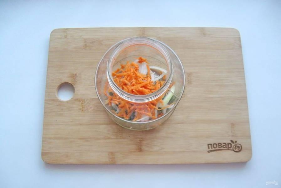 На дно банки выложите зелень, часть лука и моркови.