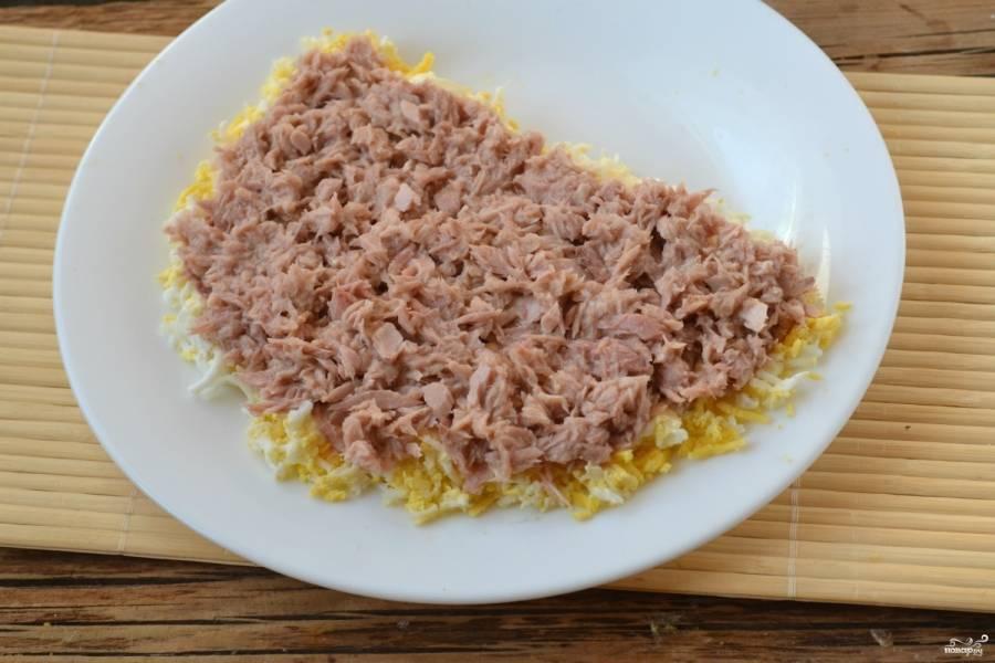 Консервированный тунец слегка разомните вилкой, не сливая масло, и выложите вторым слоем. Этот слой также покройте майонезом.