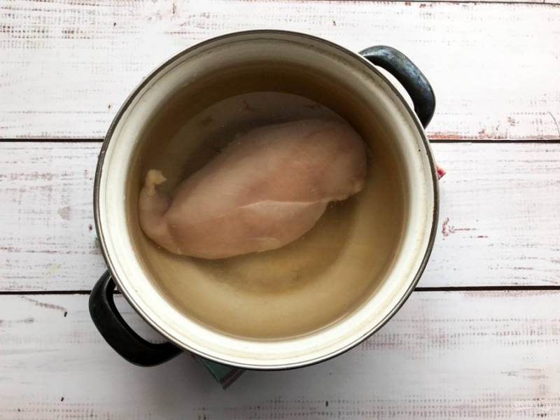 В кастрюлю налейте чистую воду, выложите куриную грудку и отправьте на огонь. Варите куриную грудку на среднем огне до готовности.