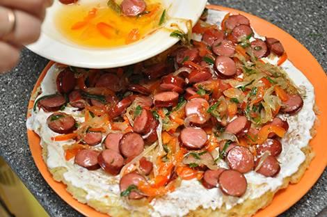 Теперь смешиваем сметану и горчицу и смазываем этим соусом основу для пиццы, наверх выкладываем обжаренные овощи с колбасками.