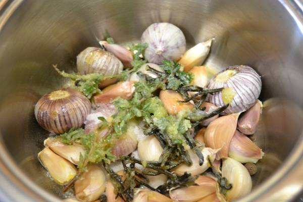 Выкладываем очищенный чеснок в кастрюлю, добавляем травки, специи и соль.